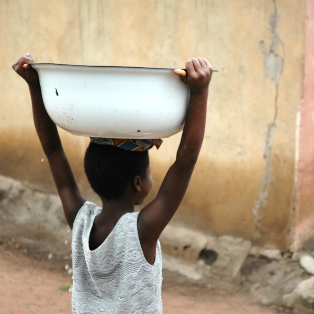 Niño cargando una palangana para recoger agua